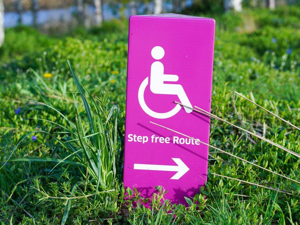 Paaltje in het gras met rolstoel icoon en de tekst 'step free route'